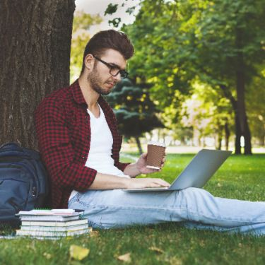 Image of a student sitting under a tree with their laptop, books and a coffee cup.